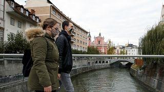 A couple cross the Ljubljanica river in downtown Ljubljana, Slovenia.
