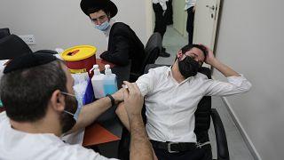 Egy zsidó férfit oltanak koronavírus ellen Bnei Brakban 2021. február 11-én