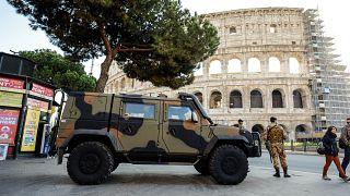 دورية من الدنود الإيطاليين تقف أمام موقع كولسيم في قلب العاصمة الإيطالية روما.