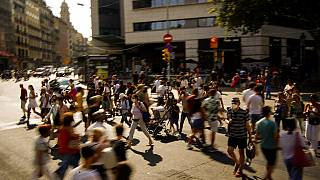 People wearing a face mask to protect against the spread of coronavirus walk along a street in downtown Barcelona, Spain, Saturday, July 3, 2021.
