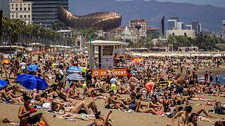 Cientos de turistas se refrescan y toman el sol en una playa de Barcelona