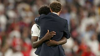 England's manager Gareth Southgate embraces Bukayo Saka after he failed to score a penalty during of the Euro 2020 final match at Wembley stadium in London,  July 11, 2021.