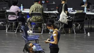 People wait after receiving the Pfizer-BioNTech COVID-19 vaccine, in a vaccination centre of Lyon.