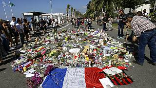 FILE - In this Monday July 18, 2016 file photo, people look at flowers placed on the Promenade des Anglais at the scene of a truck attack.