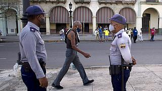 Police stand guard near the National Capitol building in Havana, Cuba, Monday, July 12, 2021