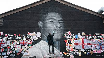 Street artist Akse P19 repairs a mural of Manchester United striker and England player Marcus Rashford in Withington, Manchester.