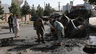 قوات الأمن الأفغانية تتفقد بقايا سيارة في موقع انفجار قنبلة في كابول في 12 يونيو 2021.