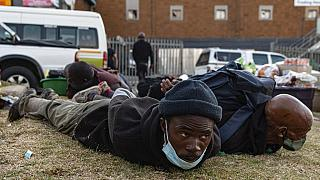 Suspect looters are held at the Bara taxi rank shops in Soweto, Johannesburg, Monday, July 12, 2021.