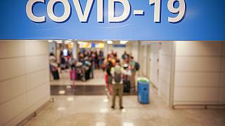 n this Aug.16, 2020 file photo, vacationers arriving in Rome from four Mediterranean countries, Croatia, Greece, Malta and Spain, line up with their suitcases at Rome airport.