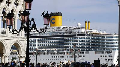 A cruise ship passes by St. Mark's Square filled with tourists, in Venice, Italy, Sunday, June 2, 2019.