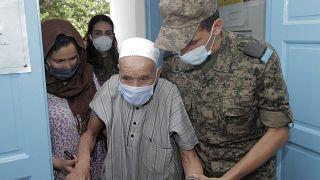 جندي تونسي يرافق عجوزاً لمساعدته في تلقي اللقاح