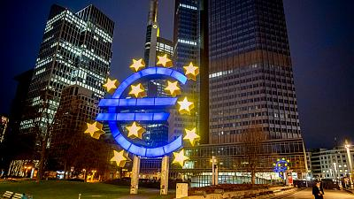 A man walks past the Euro sculpture in Frankfurt, Germany, Thursday, March 11, 2021.