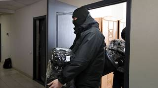 Police carry documents and computers out of the office of the Belarusian Association of Journalists in Minsk in February.