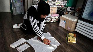 تقوم الموظفة ازدهار بإعداد الفوط الصحية في متجر خيري، تم إنشاؤه في البداية لتوزيع ملابس مجانية على المحتاجين، في العاصمة بيروت في 23 يونيو 2021