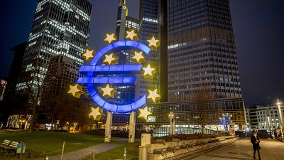 In this Thursday, March 11, 2021 file photo, a man walks past the Euro sculpture in Frankfurt, Germany.