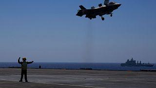 """أحد أفراد الطاقم يرسل إشارة إلى طائرة أف-35 للهبوط على حاملة الطائرات البريطانية """"اتش ام اس كوين اليزابيت"""" في البحر الأبيض المتوسط، الأحد 20 يونيو 2021"""