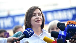 Moldovan President Maia Sandu speaks with journalists outside a polling station during parliamentary elections in Chisinau on July 11, 2021.