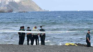 أعضاء الحرس المدني الإسباني يقفون بجوار جثة مهاجر على شاطئ جيب سبتة الإسبانية في 20 مايو 2021