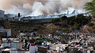 A factory burns in the background while empty boxes litter the foreground from looted goods being removed, on the outskirts of Durban, South Africa, Wednesday, July 14, 2021.