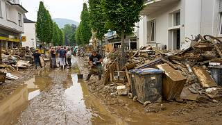 Residents clear mud and unusable furniture from houses in the city center of Bad Neuenahr, western Germany, Saturday, July 17, 2021.