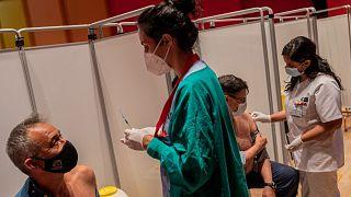 En esta foto de archivo del 13 de mayo de 2021, se administra a unos hombres la vacuna COVID-19 de Pfizer en el Hospital Severo Ochoa de Leganés, a las afueras de Madrid.