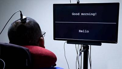 A paralysed patient looks at a screen which displays sentences that have been interpreted via a device fitted to his brain.