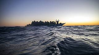 Migrants and refugees wait for assistance aboard an overcrowded wooden boat in the Mediterranean Sea