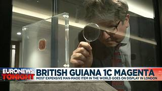 David Goldthorpe, head of books at Sotheby's, inspections the The British Guiana 1C Magenta