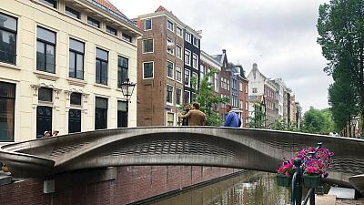 A steel 3D-printed pedestrian bridge spans a canal in the heart of the red light district in Amsterdam, Netherlands, Thursday, July 15, 2021.