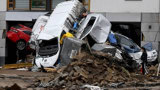 A woman looks at cars and rubble piled up in a street after the floods caused major damage in Bad Neuenahr-Ahrweiler, western Germany, on July 16, 2021.