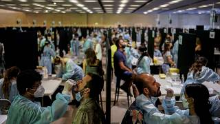 Health workers take swab samples collection for a Covid-19 antigen test ahead of the Cruilla music festival in Barcelona, Spain, July 9, 2021.