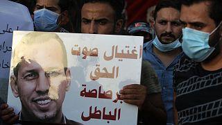 متظاهرون عراقيون يحملون لافتة تنعي الهاشمي