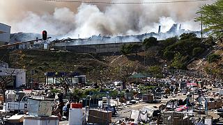 A factory burns in the background while empty boxes litter the foreground from looted goods being removed, on the outskirts of Durban, South Africa