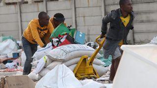 Люди забирают мешки с рисом с завода в Дурбане
