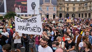Anti-vaccine protesters holds a banner that reads health pass equal apartheid during a rally in Paris, Saturday, July 17, 2021.