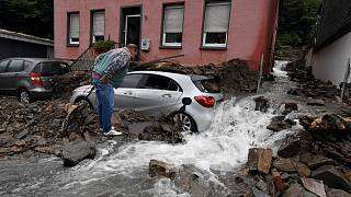 رجل ينظر إلى سيارة مغطاة بحطام ناجم عن الفيضانات، هاغن، ألمانيا، 15 يوليو 2021