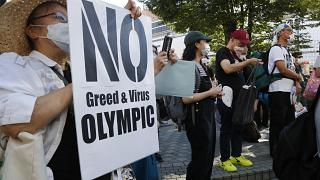 People gather for a rally in Tokyo's Shinjuku shopping district Sunday, July 18, 2021, to protest against the Olympics starting from July 23.