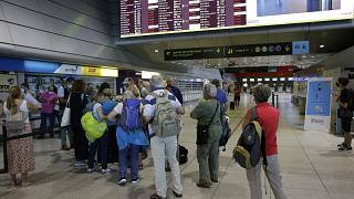 Passengers queue at the counter of Groundforce, a ground handling company at Lisbon airport, beneath a screen showing departing flights Saturday, July 17, 2021.
