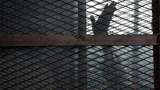 Mısır'da bir mahkum, sanıkların savunma yaptıkları sırada konuldukları kafesten el sallarken