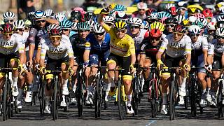 Slovenia's Tadej Pogacar, wearing the overall leader's yellow jersey,  rides with his UAE Team Emirates teammates during the last stage of the Tour de France, 18 July, 2021.
