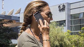 Archivo. Una mujer utiliza un teléfono frente a la sede de la firma israelí NSO, que vende el software Pegasus