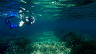 Cyprus Antiquities Department official Yiannis Violaris snorkels over submerged stone remains of the ancient harbour near Amathus ancient city, Cyprus, on July 1, 2021
