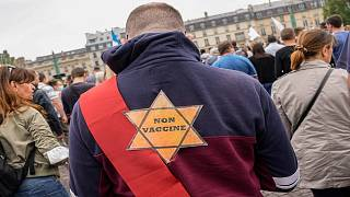 A star that reads, not vaccinated is attached on the back of an Anti-vaccine protesters during a rally in Paris, Saturday, July 17, 2021.