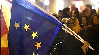 """A woman holding the national and an EU flag takes a part in a rally titled """"Walking for Justice,"""" organized by the ruling Social Democrats, starting outside parliament in 2020"""