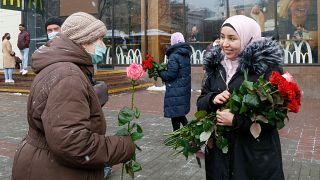 ناشطة ترتدي الحجاب تقدم زهرة لامرأة من المارة للاحتفال باليوم العالمي للحجاب في كييف، أوكرانيا، الاثنين 1 فبراير 2021.