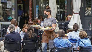 A waiter serves food at a restaurant terrace in Versailles, west of Paris, Thursday, July 15, 2021