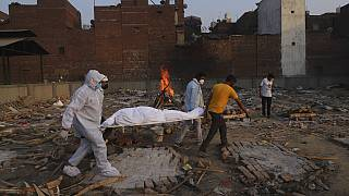 Family members and volunteers carry the body of a COVID-19 victim for cremation in New Delhi, India.