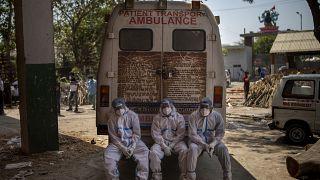 مسعفون بجانب سيارة إسعاف بالقرب من محرقة لجثث الموتى، في نيودلهي، الهند.