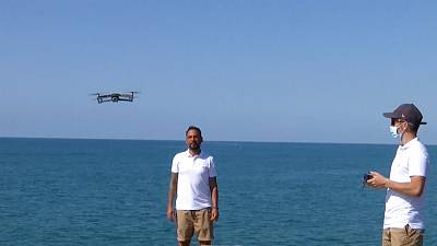 Drones are operated above the Sitges shore to monitor COVID-19 social distancing measures.