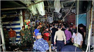 عناصر أمنية ومدنيون يتفقدون موقع التفجير الدامي الذي نفذه تنظيم الدولة الإسلامية في سوق الوحيلات بمدينة الصدر بالعراق